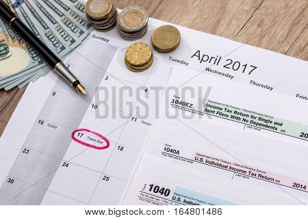 calendar 2017 tax forms with pen and dollars.