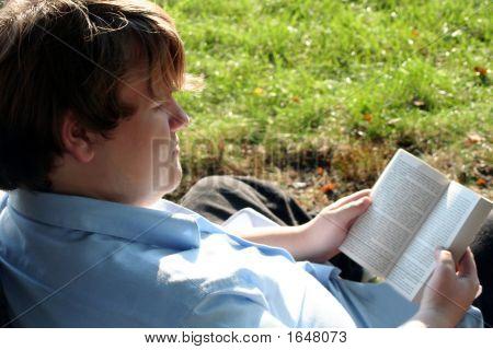 Teen Engrossed In Book Outdoors