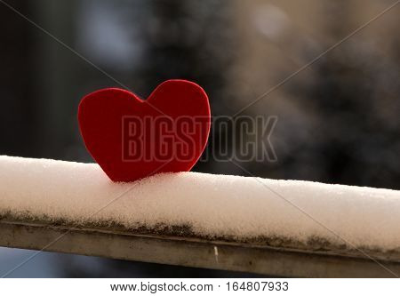 Lonely red heart on snowy rusty railing