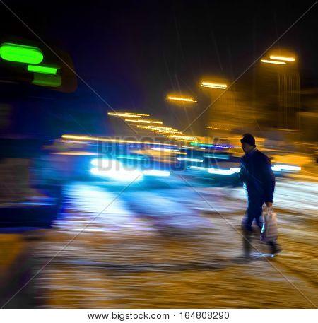 Man on zebra crossing at night. Intentional motion blur