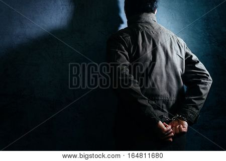 Arrested male criminal with handcuffs facing prison wall as copy space