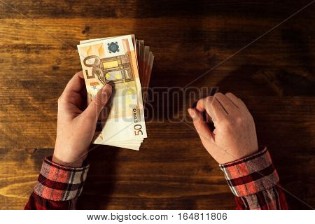 Woman offering money loan in euro currency banknotes top view of business office desk