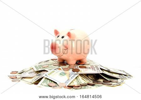 Pink piggy bank standing on coins and bills, suggesting money savings concept