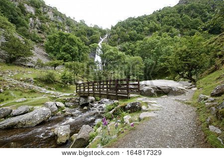 Aber Falls Bridge with river bellow and waterfall in the background,  Summer with  trees and plants surrounding landscape. Abergwyngregyn North Wales UK