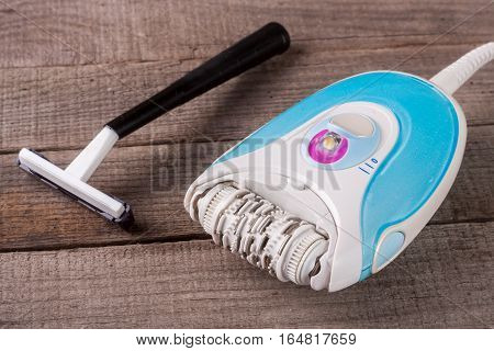 electric epilator with a razor on a light wooden background.