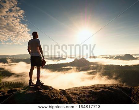 Tourist With Red Baseball Cap Sporty Shorts Stand On Cliff Edge