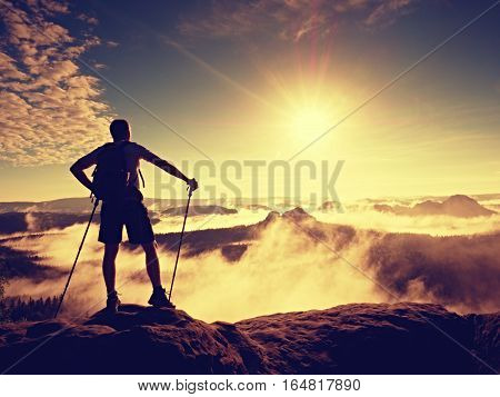 Tourist With Sporty Backpack And Poles In Hands Stand On Cliff