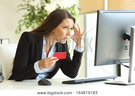 Worried businesswoman wearing suit having problems buying on line with credit card in a desktop at office