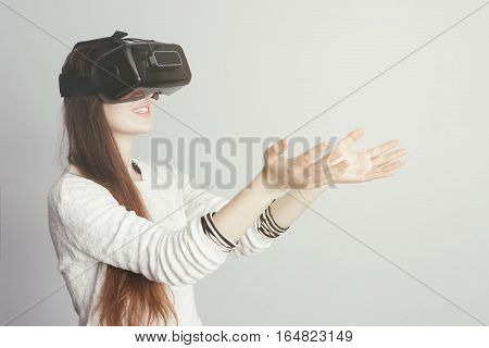 Young surprised girl with glasses of virtual reality looks forward and try to hold something