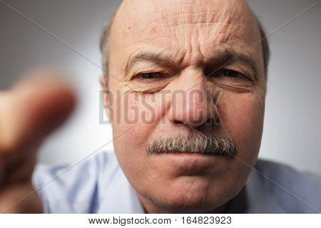 Elderly man dissatisfied frowns and looks sullenly. Poking his finger ahead