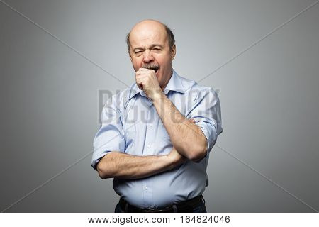 Bald man covers mouth with fist yawning with fatigue and sleepiness. Tired of the work and desire to sleep