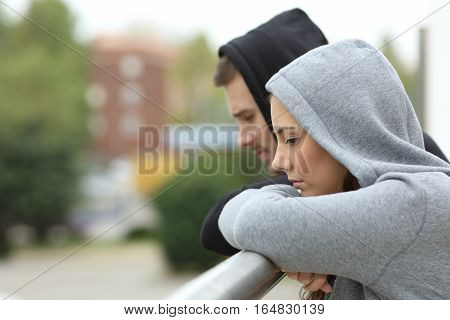 Side view of a sad couple of teens looking down after break up in a balcony of a house with an urban background