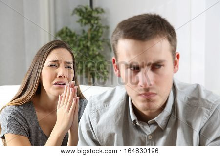 Wife asking for forgiveness to her ex husband after conflict sitting on a couch in the living room of a house