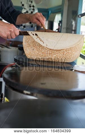 Hands flipping a crepe using wooden spreader and scraper