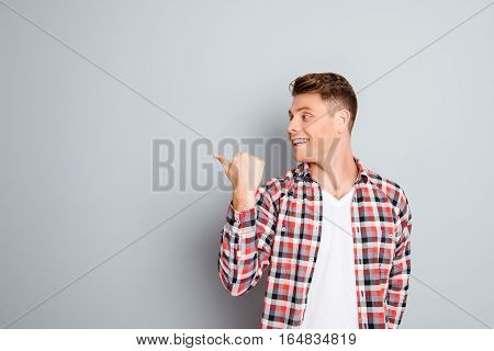 Young Cheerful Man Showing Direction On Gray Background