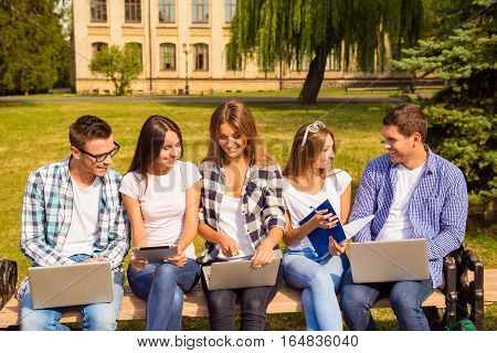 Happy Five Diverse Classmates Sitting On Bench And Study Up