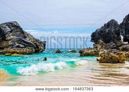 Snorkelers in the aqua marine colored water of scenic Horseshoe Bay in Bermuda.