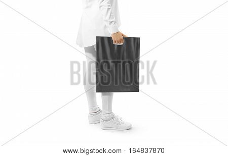 Blank black plastic bag mockup holding hand. Woman hold dark carrier sac mock up. Grey bagful branding template. Shopping carry package in persons arm. Promotional packet for logo branding.