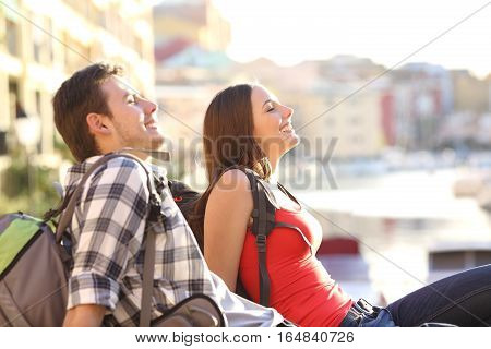 Side view of a couple of teen tourists relaxing on vacations sitting on the floor and breathing fresh air
