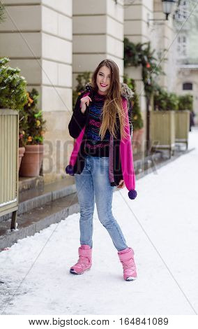 Young lady with long blonde hair and perfect makeup looking at the camera and smiling, outdoor shooting in the city. Winter look in stylish clothes. Light colors photo