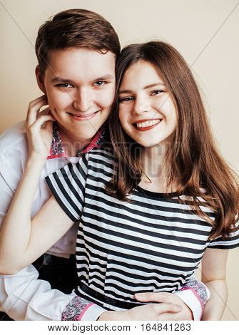 couple of happy smiling teenagers students, warm colors having a kiss, lifestyle people concept close up
