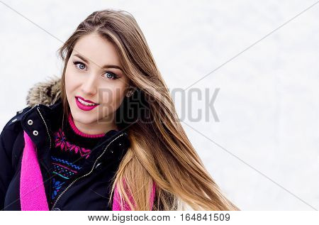 Young lady with long blonde hair and perfect makeup looking at the camera and smiling, outdoor shooting in the city. Winter look in stylish clothes.Close up portrait on white background
