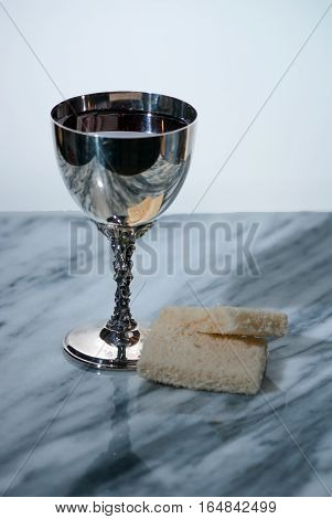 A sliver chalice with a drink and bread to symbolize the blood and body of Christ