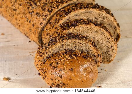 Fresh bread slice with sunflower seeds on wooden table and Wheat