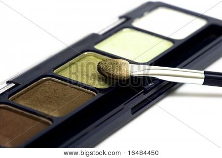 green make-up eyeshadows and cosmetic brush