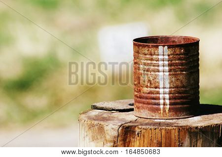 Rusted tin can sitting on tree stump