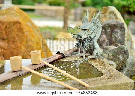 Japanese washbasin tsukubai with a dragon fountain and bamboo ladle.