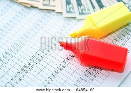 Pair of felt tip pens near money on paper background with digits