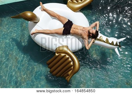 Top Shot Of Handsome Male Model Posing Topless On Air Bed Keeping Hands Behind His Head, Looking Rel