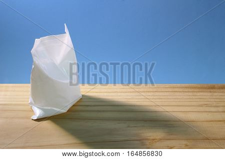 White Plastic Bag on a Wooden Background
