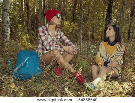 Two Young Tourists With Backpacks Relaxing In Forest