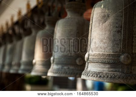 Row of religious bells in a Buddhist shrine. Asian Buddhist monastery bronze ornamental bell at a temple in Thailand