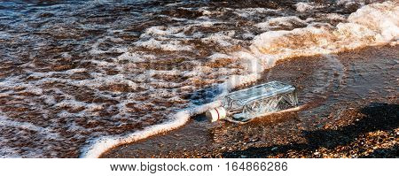 An empty bottle on the beach with a message