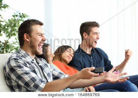 Excited men watching tv and bored girlfriends sitting on a couch in the living room at home