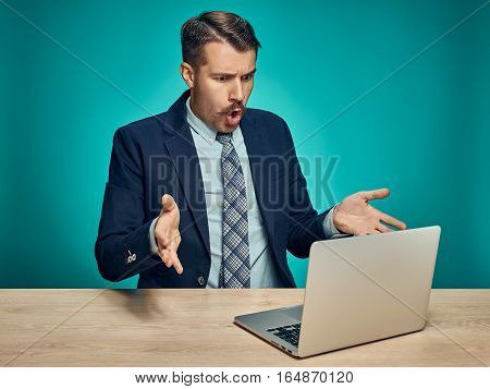 The sad and puzzled young man in a business suit working on laptop at desk on blue studio background