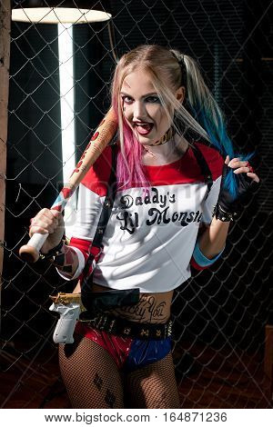 Girl in costume Harley. She stands with bat and gun. Close up. Cosplay.