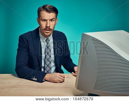 The sad young man in a business suit working on computer at desk on blue studio background