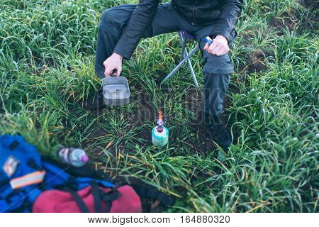 Man On Stool In Field With Burning Camping Gas.
