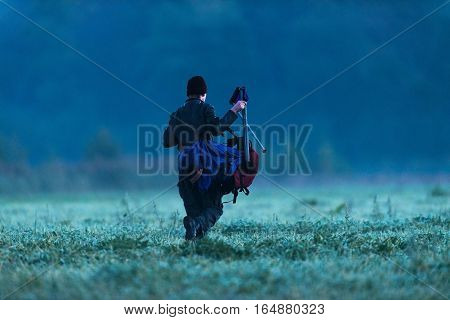 Young Man Walking With Backpack And Stool Into Field At Cold Morning.
