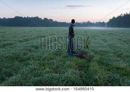 Young Man Standing With Stool And Backpack In Misty Meadow At Dawn.