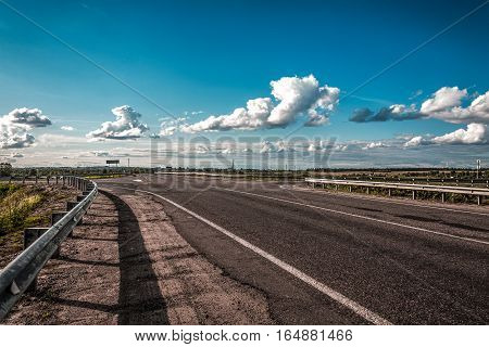 the empty asphalt road in the summer evening against the background of the sky