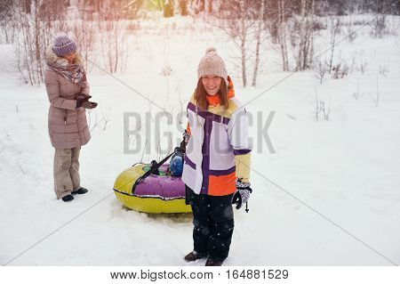 Group of smiling happy people having fun on snow hill. Two women and child sliding on tubes.winter vacation concept.