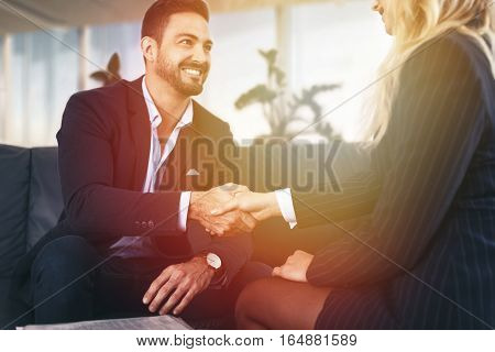 Businessman handshake with businesswoman in sunset at office