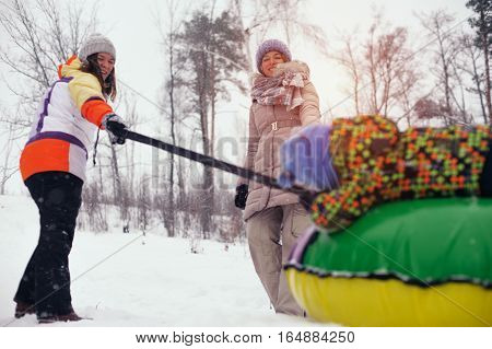 Two women and child sledding on snow tubing. Group of caucasian people having fun on snow hill. Winter vacation.