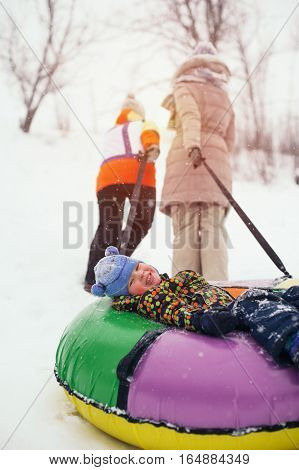 Happy smiling child lying on snow tube. Group of people having fun on snow hill. Winter vacation concept.