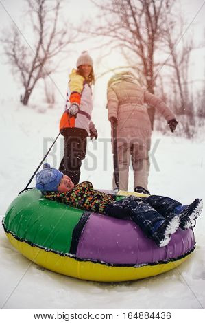 Happy smiling boy lying on snow tube. Winter vacation. Two women and little child having fun on snow hill.
